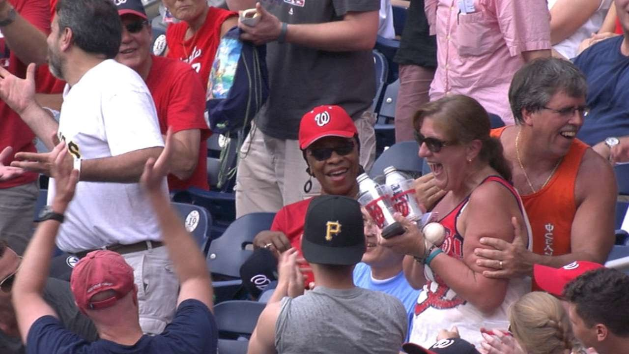 Fan catches a foul ball with two beers in her hands