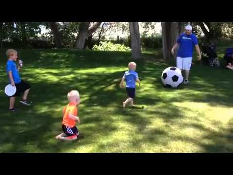 Father kicks large soccer ball knocking down boy