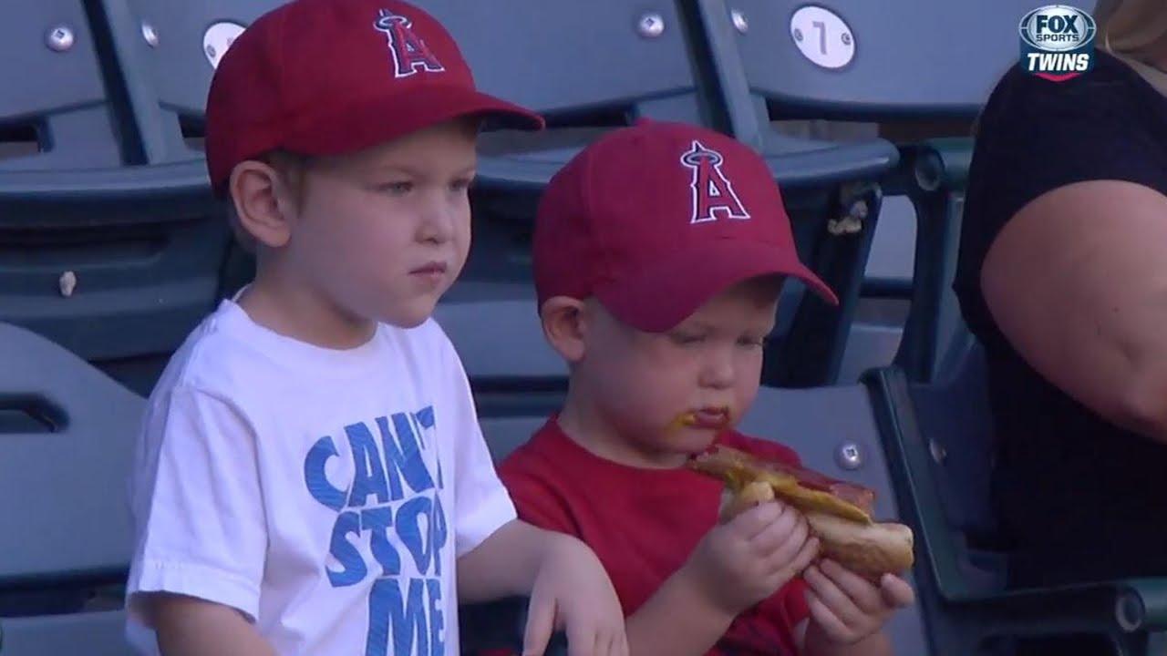 Kid struggles to eat hot dog at baseball game