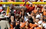 Texas Longhorns players crowd surf head coach Charlie Strong