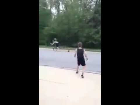 Kid throws basketball at young lady riding a bicycle