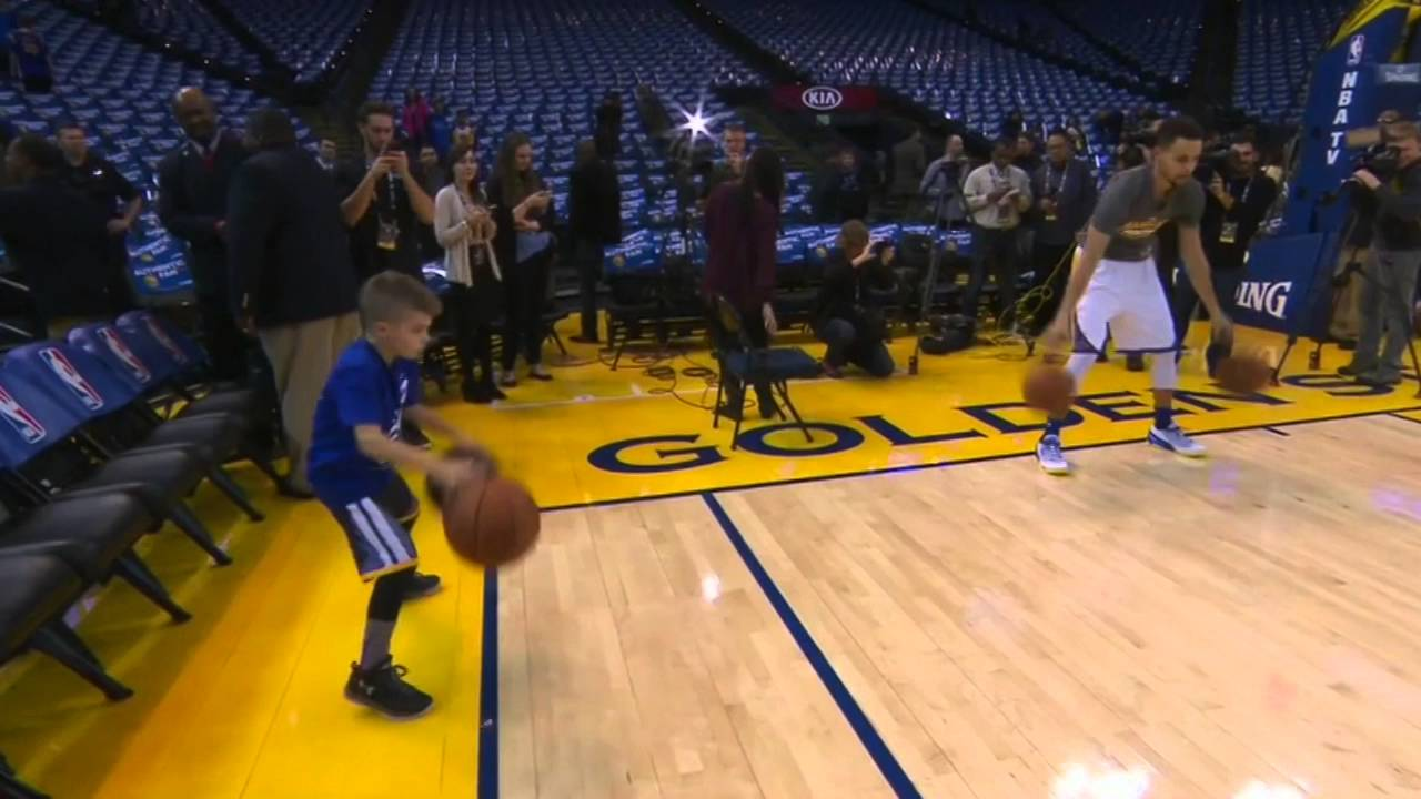 Steph Curry does his pre-game dribbling ritual with a young fan