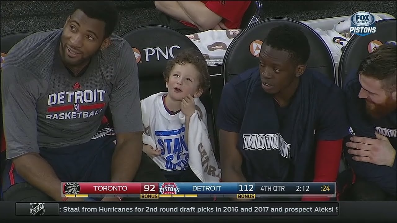 Andre Drummond brings a young fan down to chill on the Pistons bench
