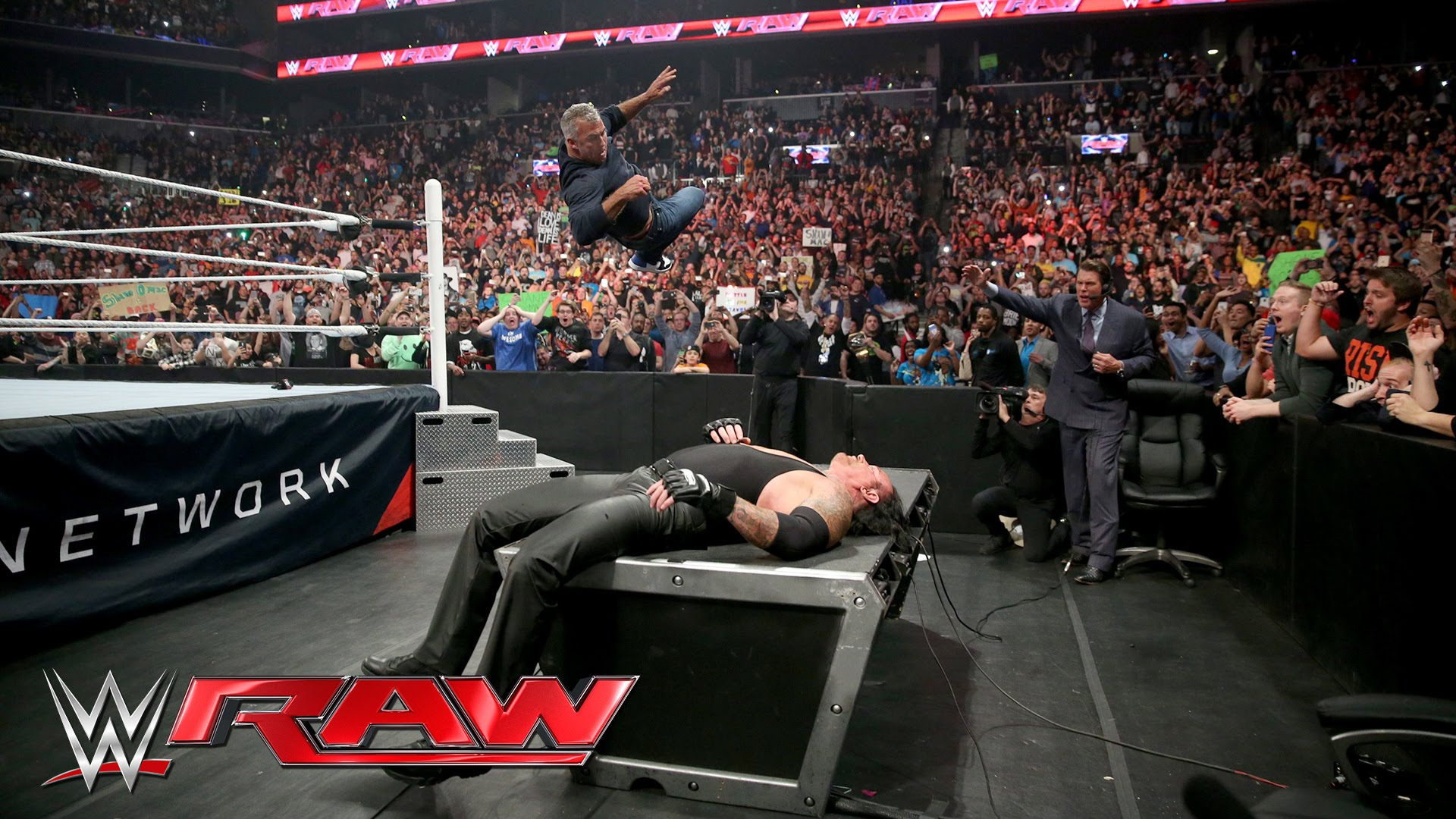 Shane McMahon elbow drops The Undertaker through table