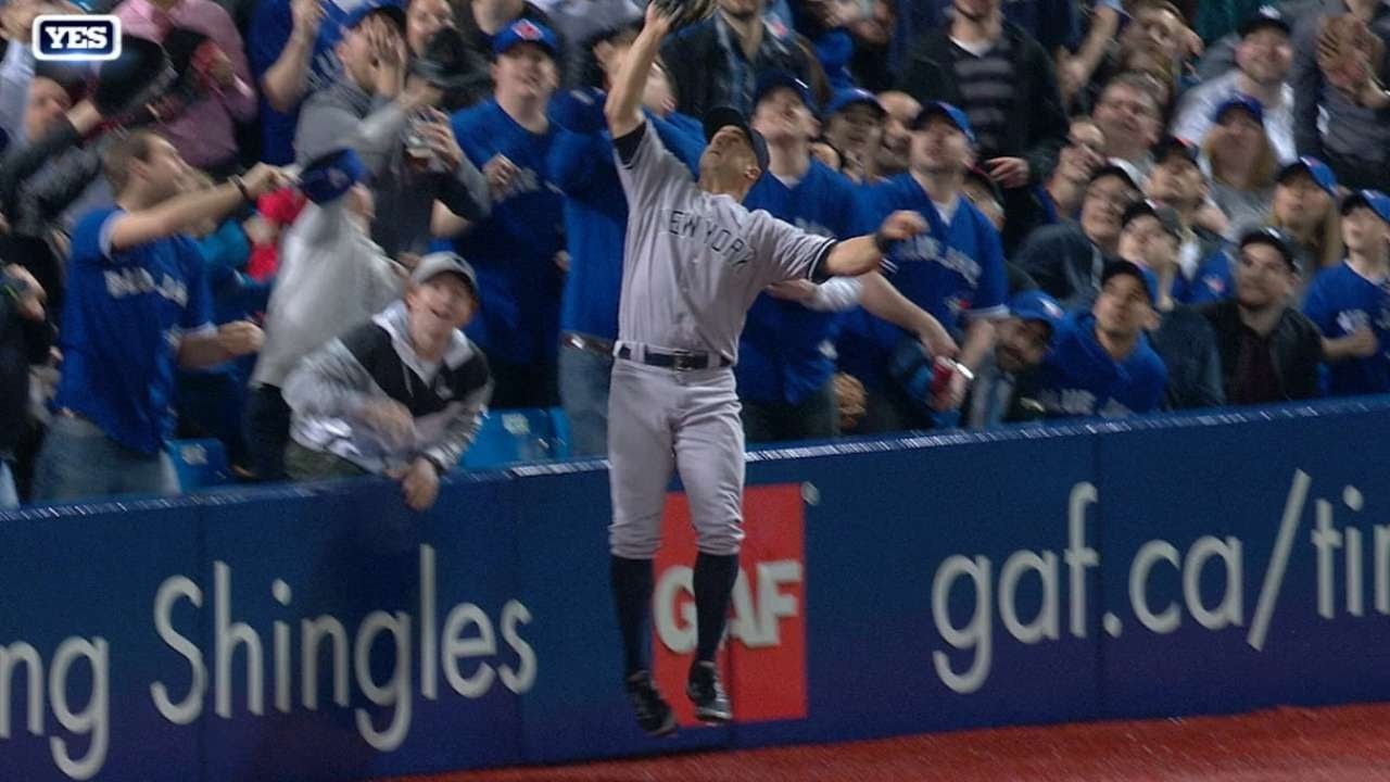 Brett Gardner leaps into the stands to make the catch