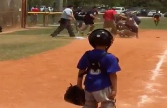 Little leaguer sadly watches fight breakout on the diamond